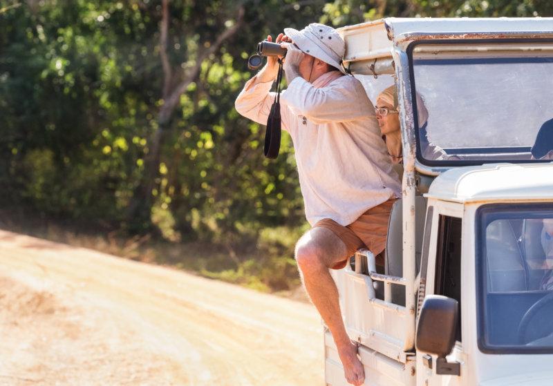 Mann blickt mit Fernglas aus dem Jeep heraus