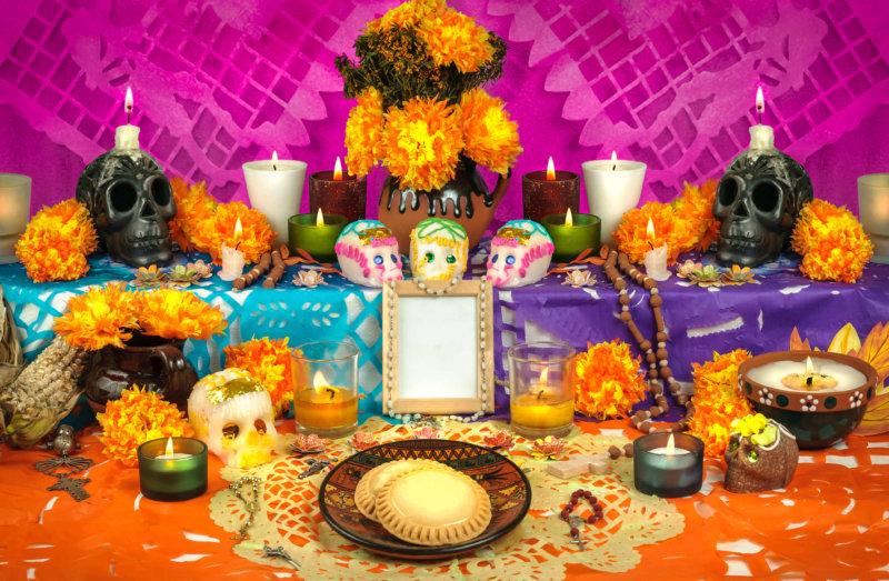 Altar für den Día de los Muertos mit Schädeln und Kerzen