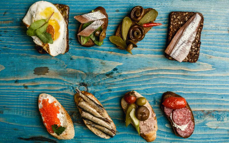 Brotscheiben mit Ei, Fisch, Gurken und mehr