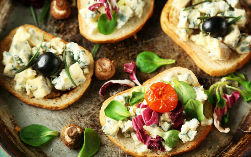 Belegte Brote mit Salat, Tomaten, Oliven, Käse