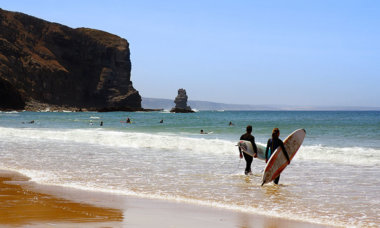 Two surfers ready to enter the sea in Arrifana Beach, Algarve Portugal