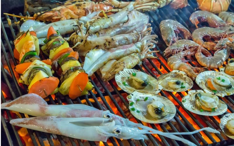 Griechische Küche: Meeresfrüchte auf dem Grill mit Flammen Closeup