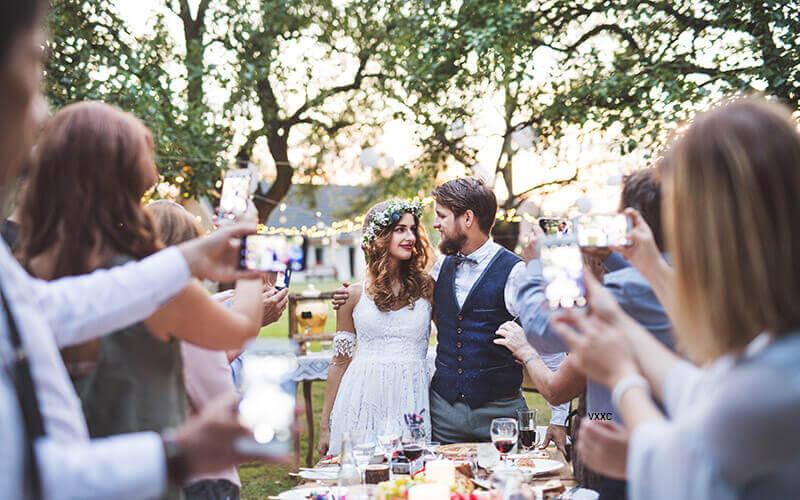 Brautpaar inmitten von Smartphones