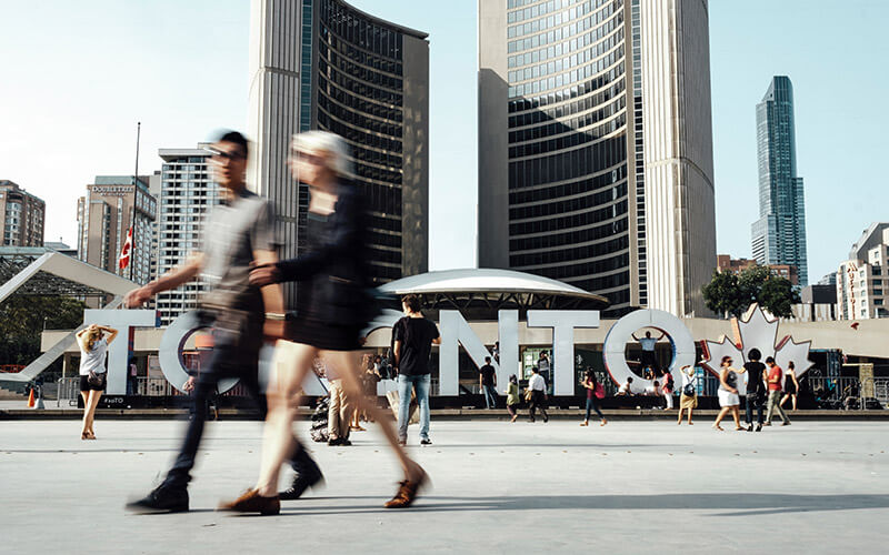 Leute huschen über einen Platz in Toronto