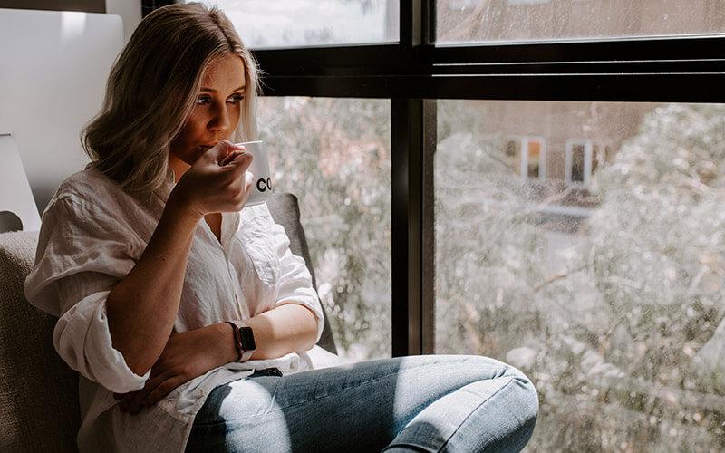 Frau mit Tasse in der Hand schaut zuhause aus dem Fenster