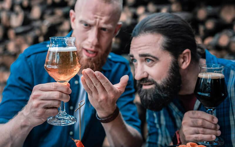 Zwei bärtige Männer schauen sich neue Sorte leichtes Craft Beer an - © Depositphoto - Viacheslav Iakobchuk