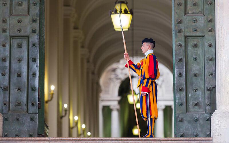 Ein Mitglied der päpstlichen Schweizergarde, Vatikan im Eingang des San Pietro Gebäudes © Depositphoto - Andrea Izzotti