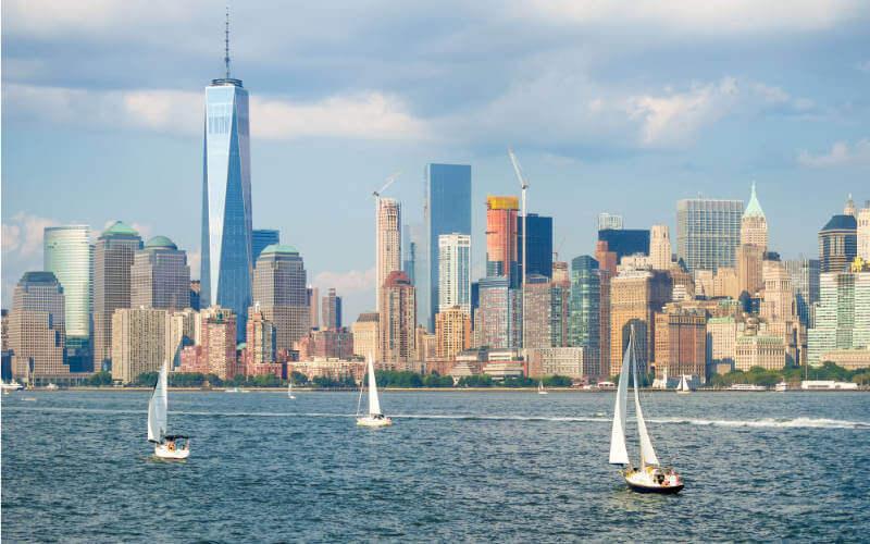 Segeltörn Manhattan: Die Skyline von New York mit Segelbooten an einem Sommertag
